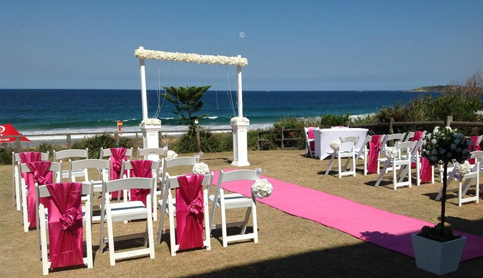 White ceremony arch with white Americano foldable chairs and Hot pink carpet aisle runner
