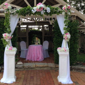 White timber arch with artifical greenery and flowers